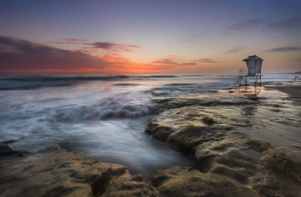At sunset, the lifeguard stand at the Coronado beach is empty and the water is lively crashing against the natural terrain