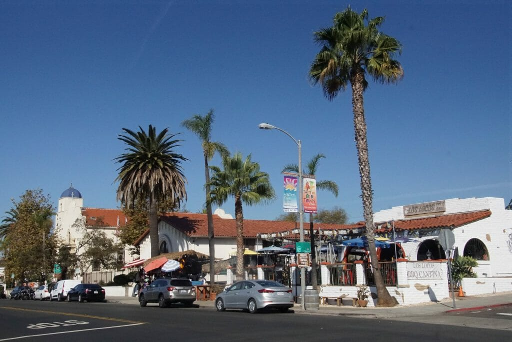 On a clear day, pedestrians walk around Old Town San Diego and its mexican style buildings