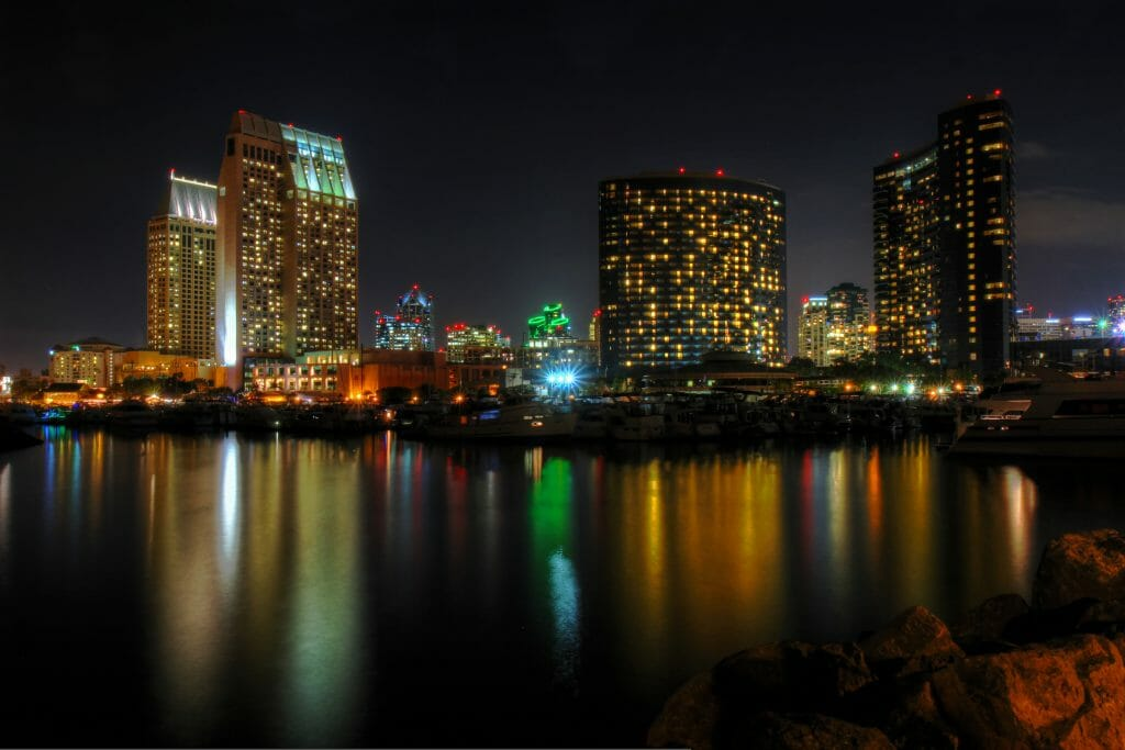 The night lights of the San Diego skyline twinkle and reflects against the water