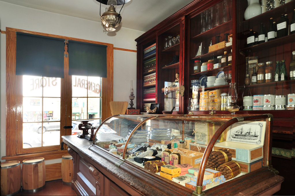An old time general store with a wood and glass display case with knick knacks inside, the wall is lined with bottles and packages nd the sun shines through the window