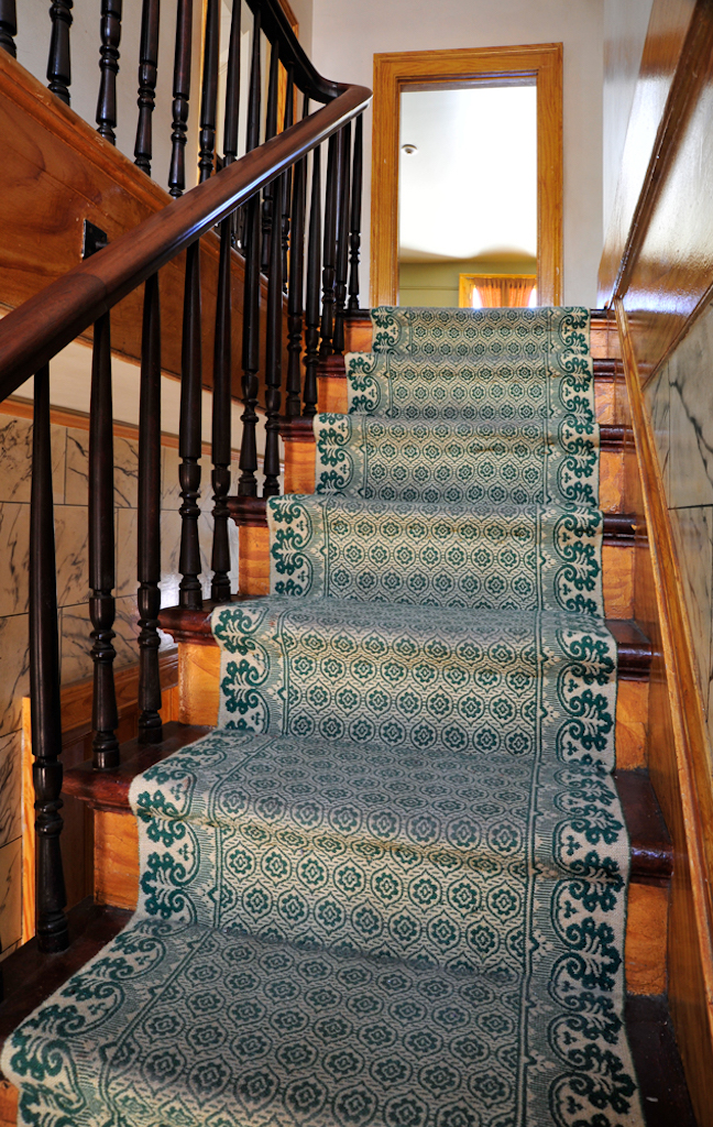 A light wood staircase with a green liner runs up to a brightly lit area of the second floor