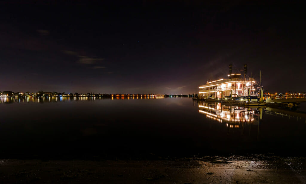 Night view of an authentic, vintage, American riverboat with two chimneys resembling the steamboats used in the 1800s in Mississippi river. A view of Mission Bay and pier in San Diego, southern California, USA.