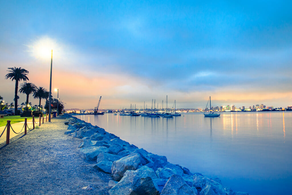 View of San Diego California at sunset with boats and buildings seen across the water