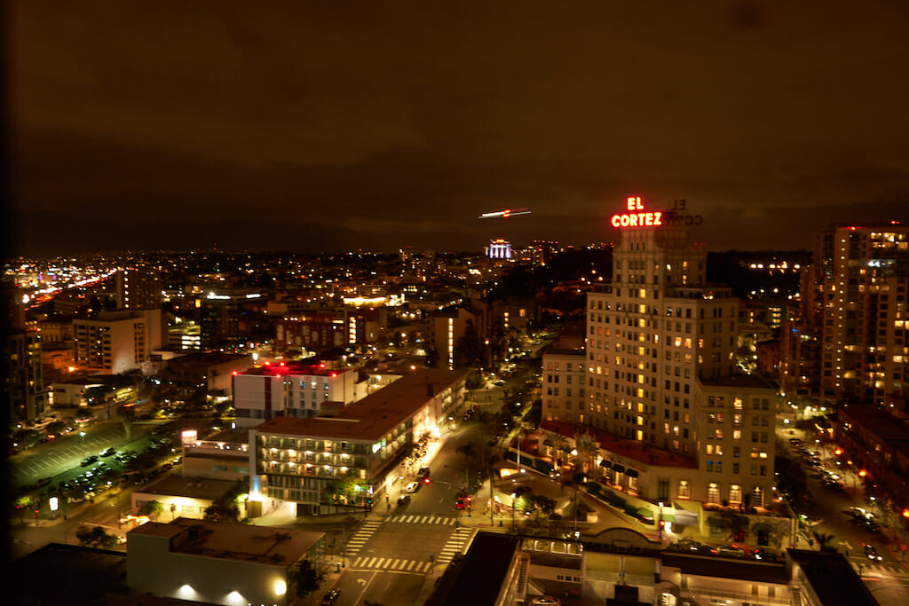 The lights radiate from the buildings as the hum of cars and people buzz below on a San Diego night