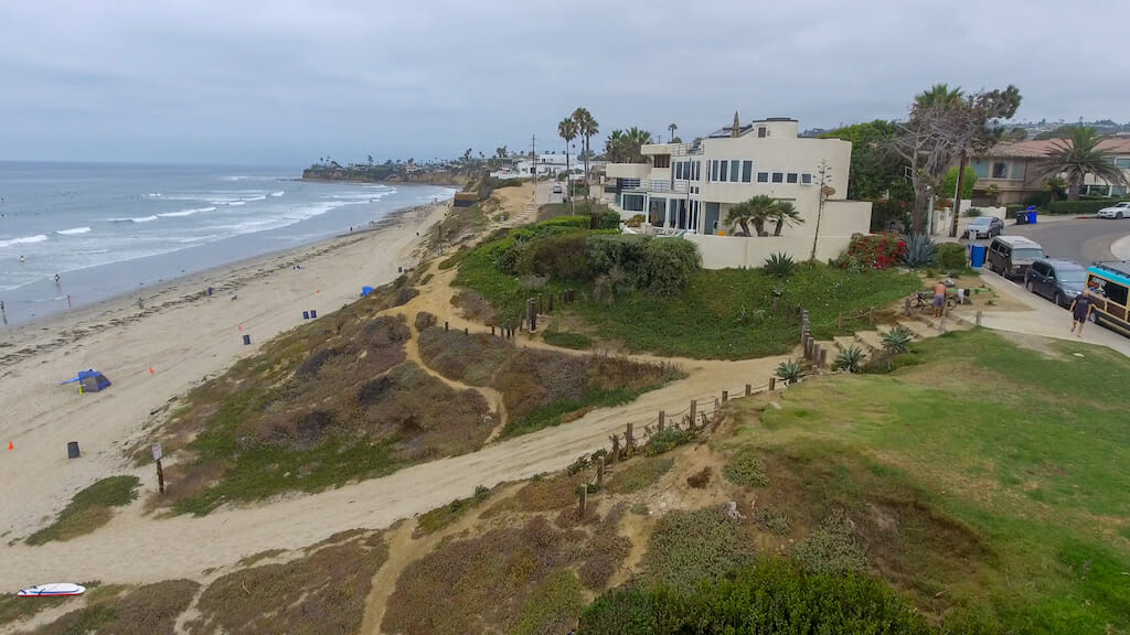 The water crashes onto the La Jolla shore as people idly walk across the beach and the buildings overlook the beautiful horizon