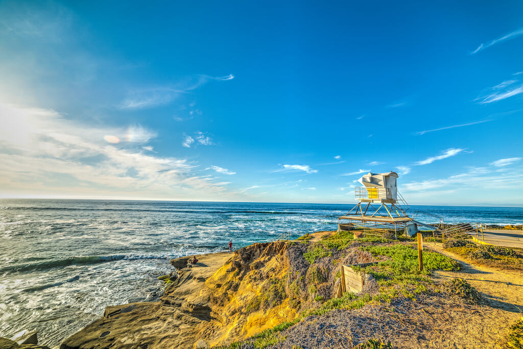THe sun is shining on a lifeguard station that is peacefully overlooking the beautiful La Jolla shores
