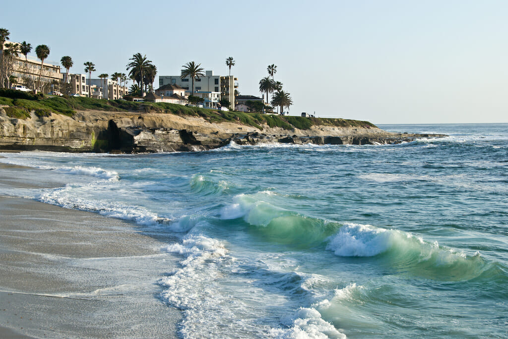 Water crashing onto the sand of the La Jolla shores with cliffs filled with buildings and greenery in the background
