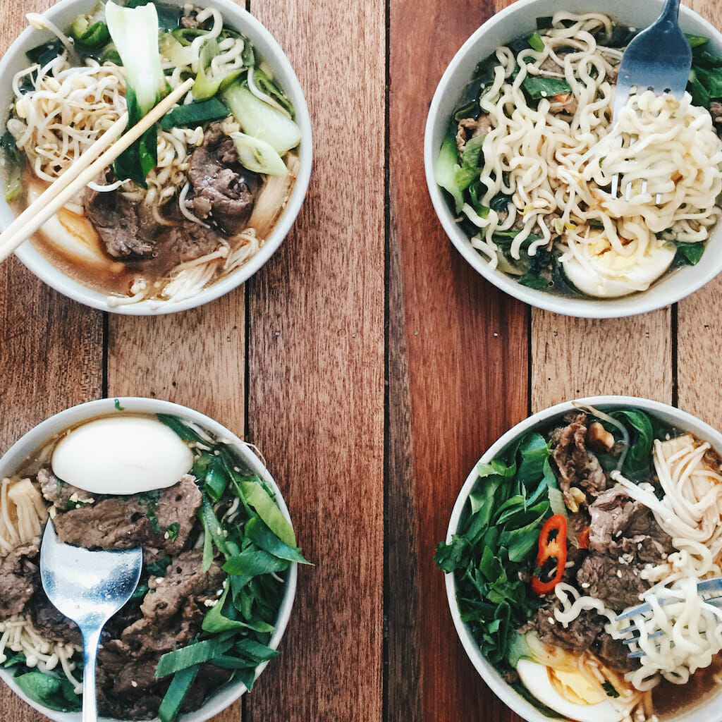 Four separate bowls of different ramen in the four corners of a brown wood table with chopsticks and spoons