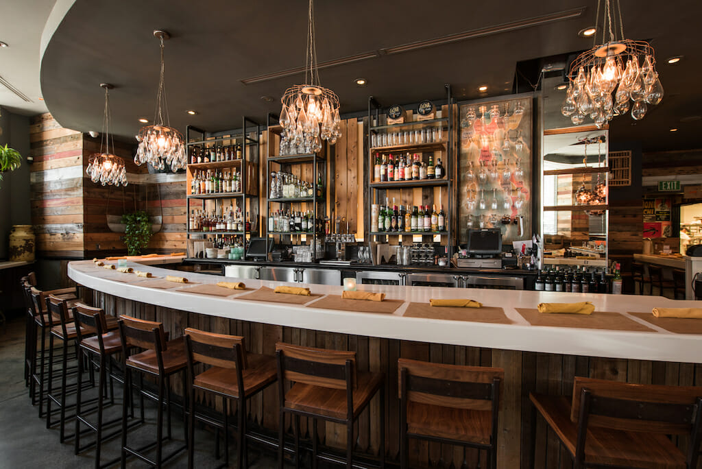 Natural wood bar with selves filled with prime alcohol lit by humble chandeliers