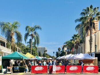 San Diego Farmers Market in Little Italy - Vendor stalls on closed off street under palm trees