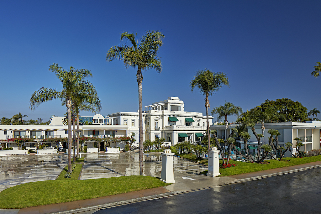 The outside of a beautiful white hotel with palm trees all around