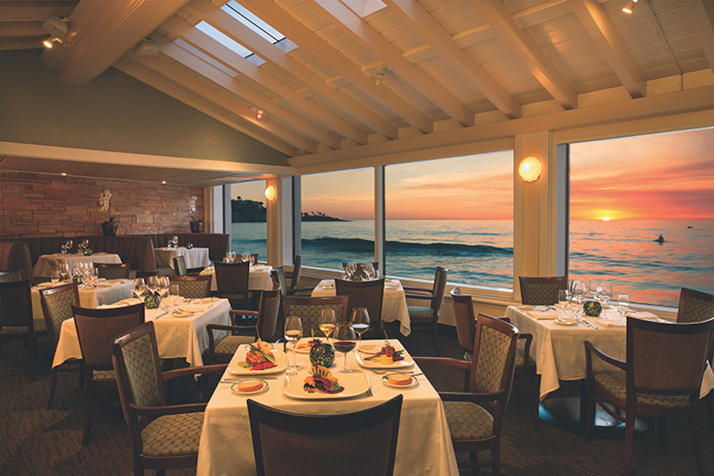The sun setting out the window over the water with the peaceful dining room empty