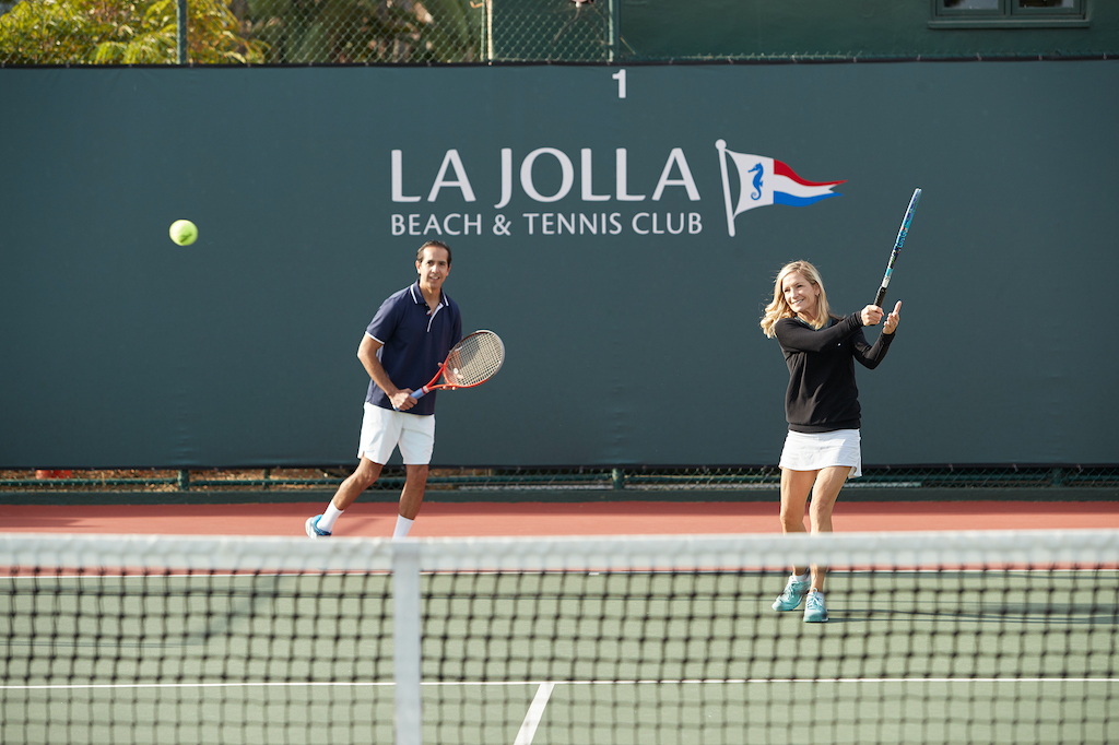 Two white people playing tennis in the bright sun