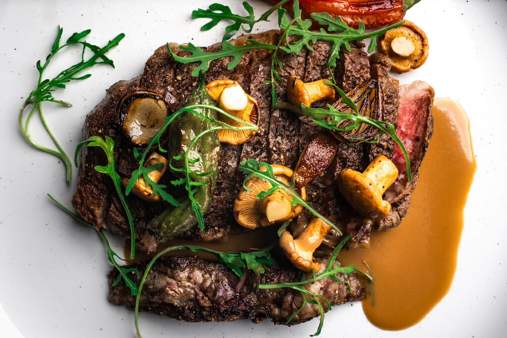 A steak on a white plate with greens and mushrooms scattered over it