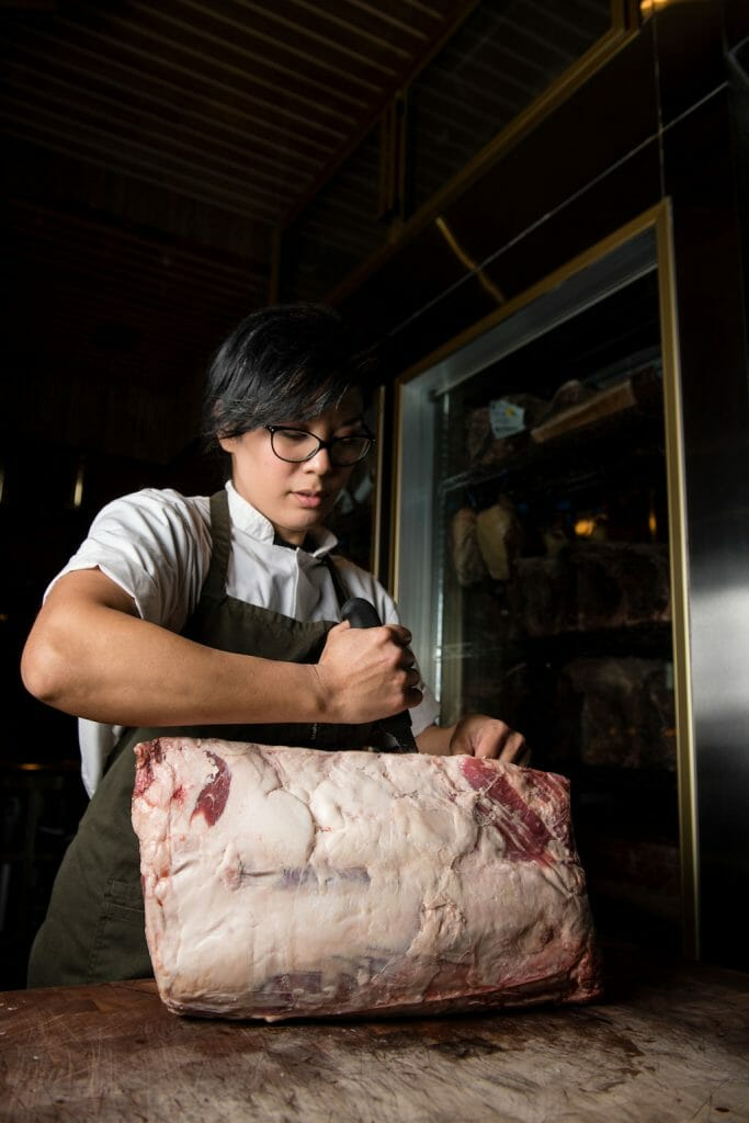 Woman using her chef knife to carve into a raw hunk of meat with power and determination