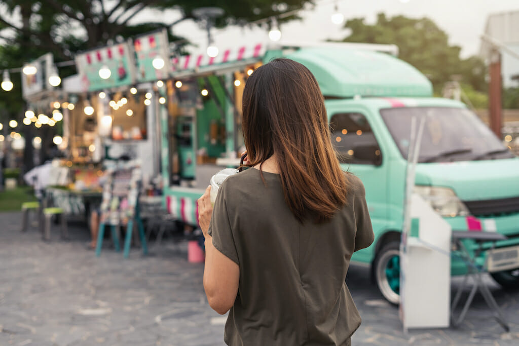 Young asian woman walking in the food truck market