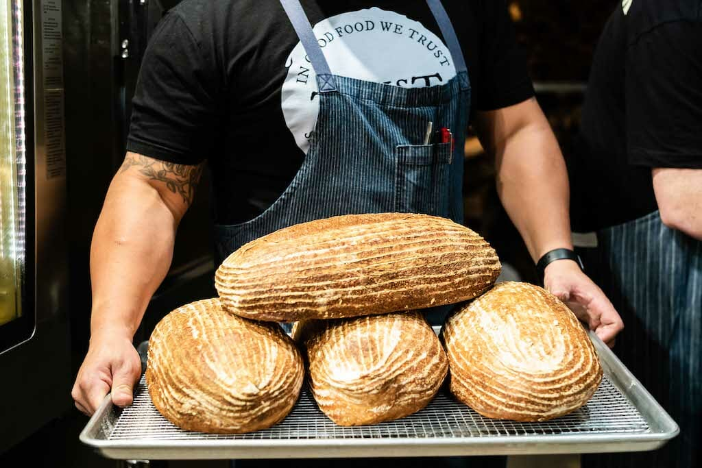 Incredible burly man carrying a beautiful tray of sourdough bread loaves