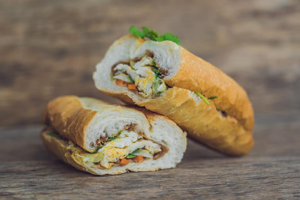A delicious Vietnamese Bahn Mi sandwich on a wooden background.