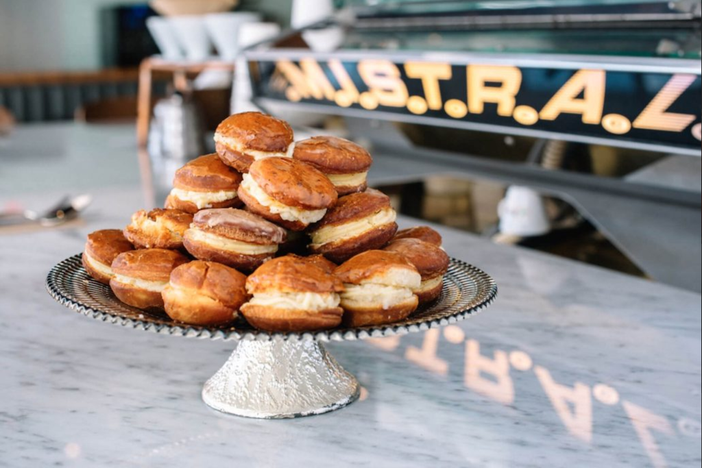 Several Cream Puffs stacked elegantly on a cake stand just outside, waiting to be taken