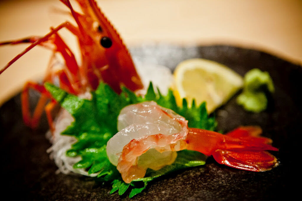 Shrimp head with sashimed shrimp and shinso leaves on a black plate