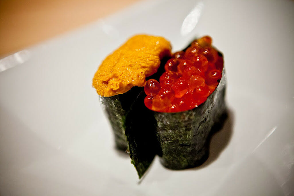 Two different pieces of sushi one with urchin and the other with fish eggs