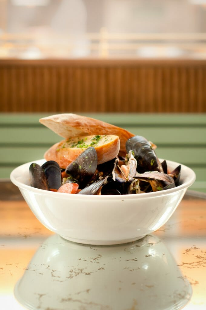 In a simple white bowl, beer braised mussels sit in their juices with two slices of crostini lay atop it