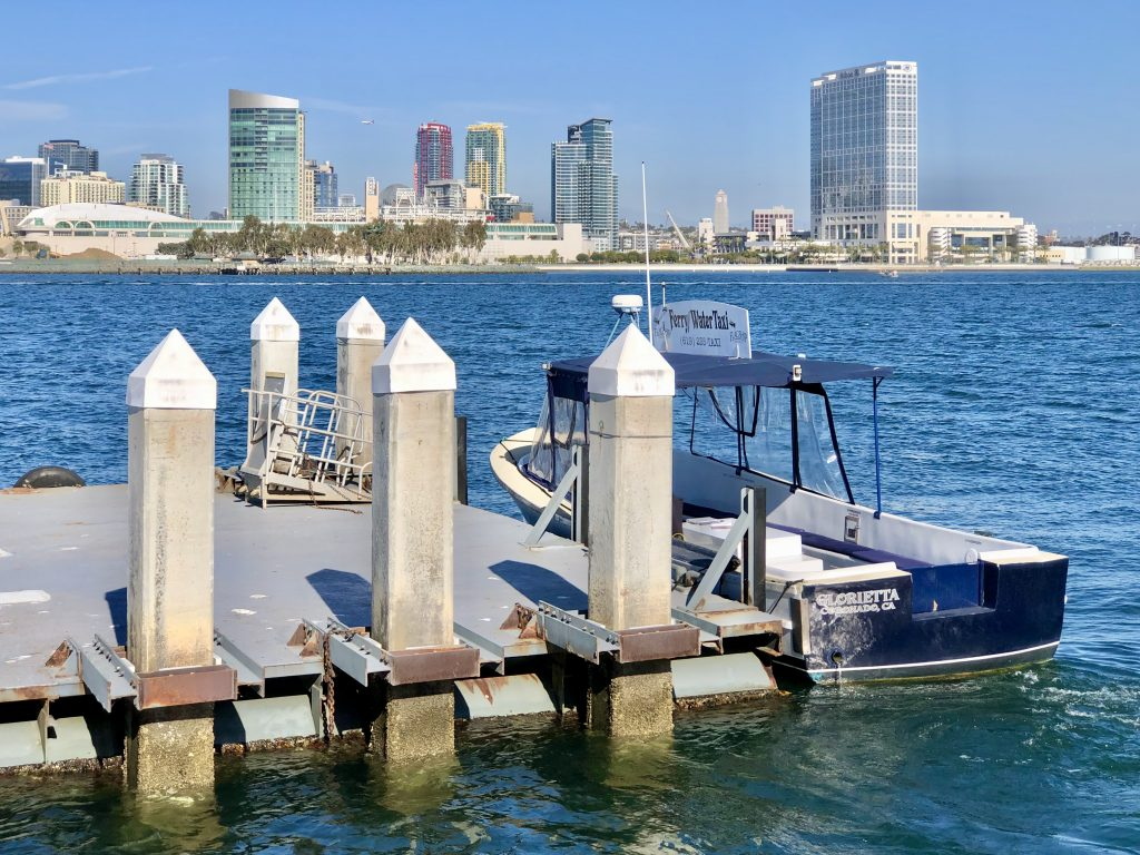 Cornado Ferry Landing Water Taxi with San Diego Skyline in the back on a sunny day with blue skies