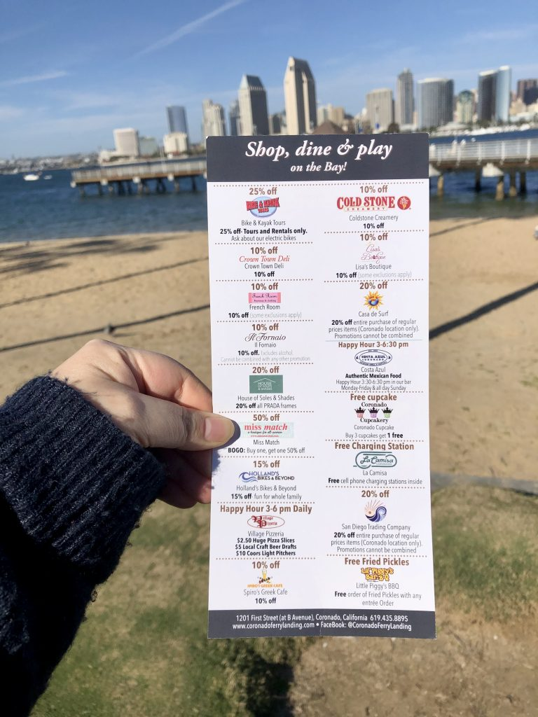Free Discount card for shops and restaurants at Coronado Ferry Landing held up in front of San Diego Skyline