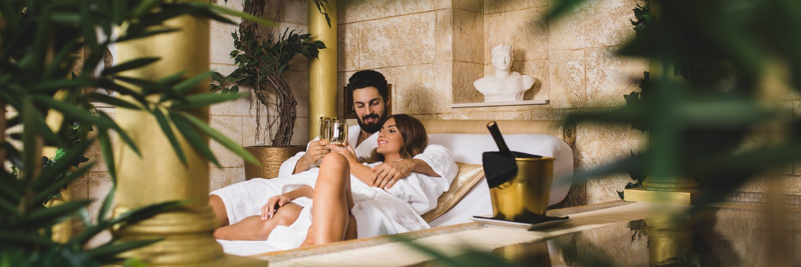Beautiful young couple enjoying and relaxing in SPA center and drinking wine