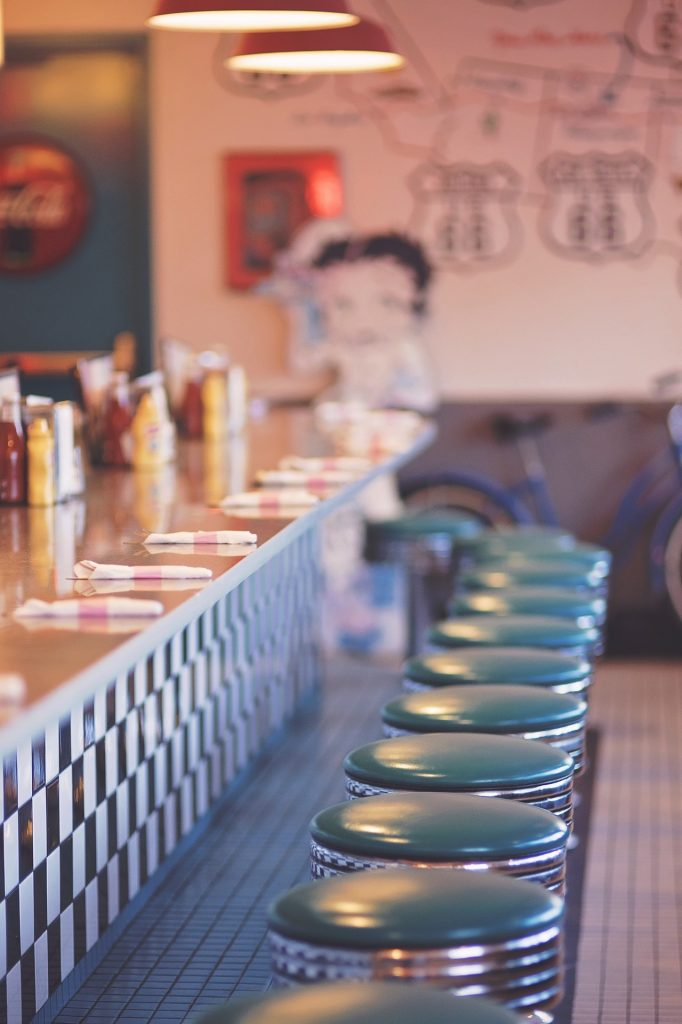 Counter of a 50's diner with swivel stools and a blurry Betty Boop in the back