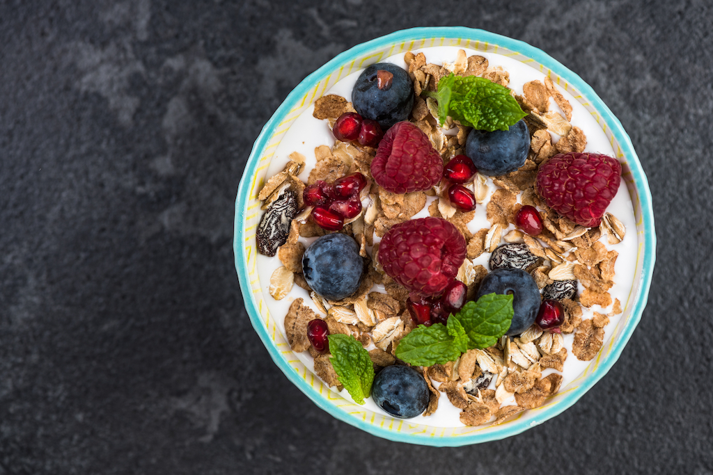 Homemade healthy brunch or breakfast bowl, top view on granite table.