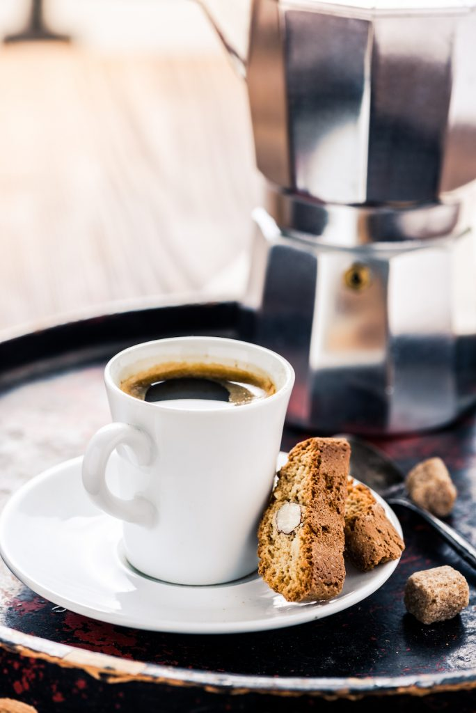 a kettle coffee pot next to a steaming cup of coffee and biscotti