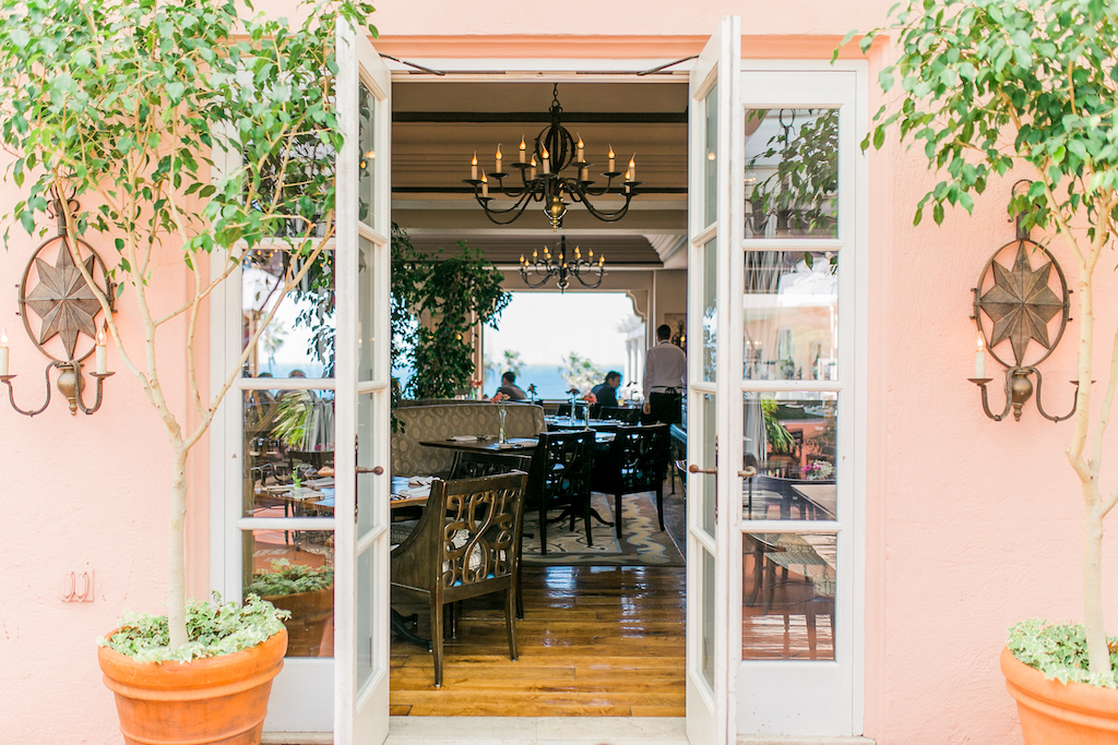 Pink walls break to a white glass door entrance to an elegant lit up dining room
