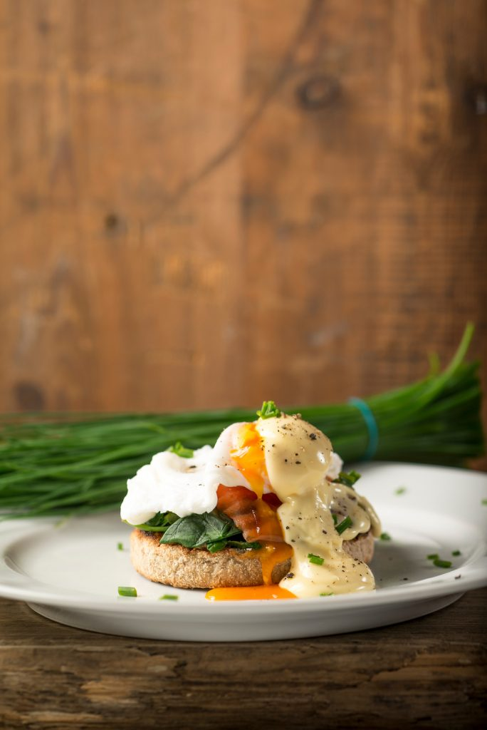 Smoked Salmon, poached egg and spinach on a toasted English Muffin with herbs in the background