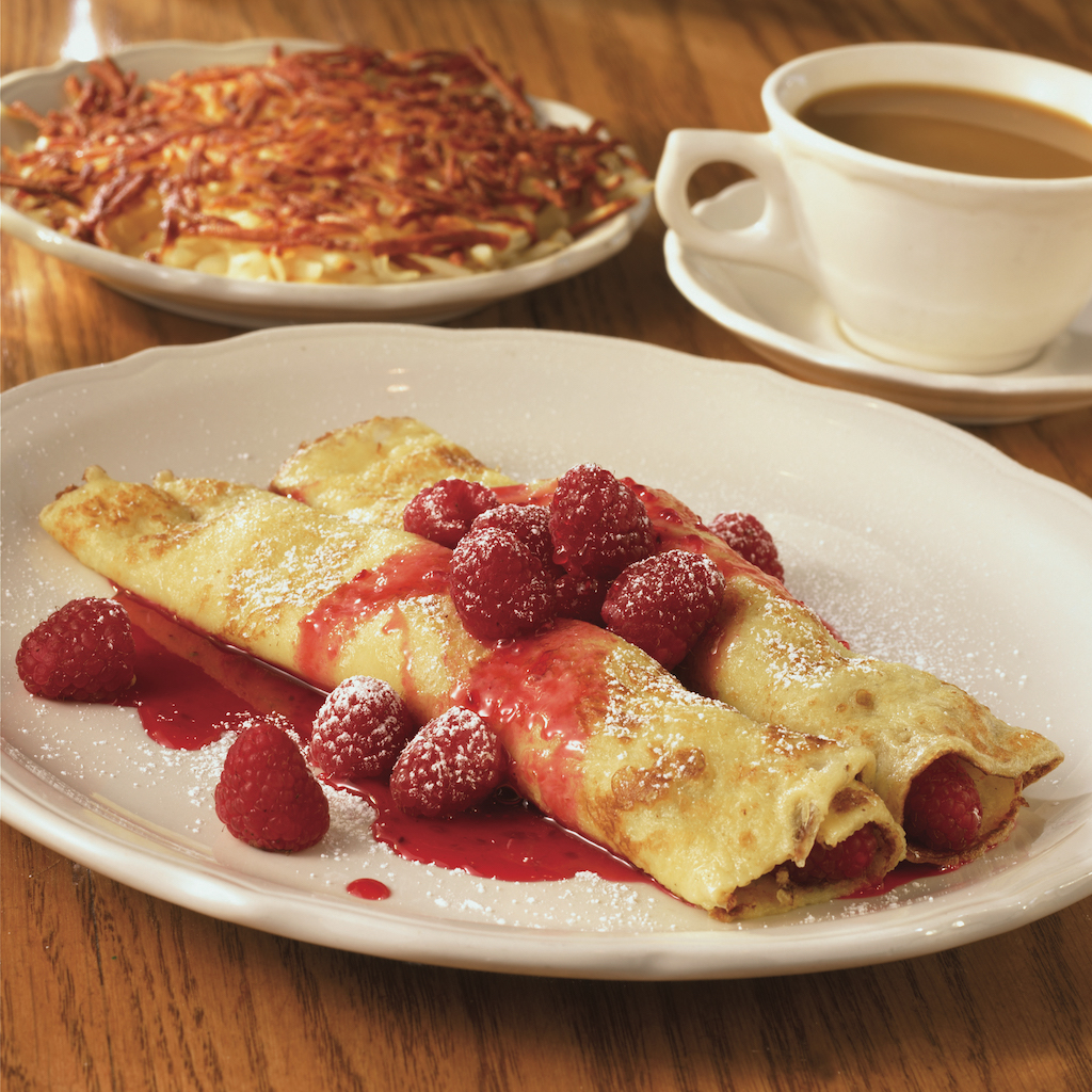 Two rolled crepes laying side by side with a raspberry topping in front of another dish and a cup of coffee