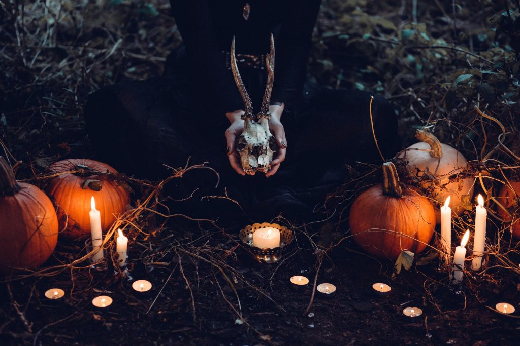 Witch holding a deer skull surrounded by pumpkins and candles