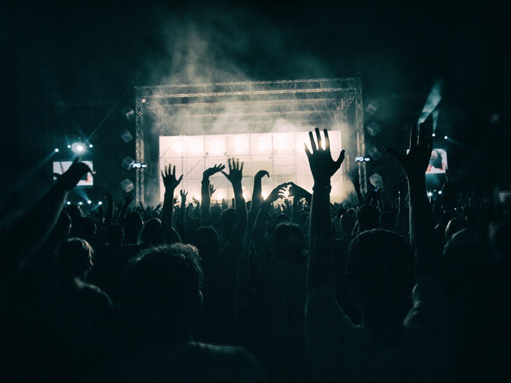 Crowd at a lively concert dancing a distance from the brightly lit stage