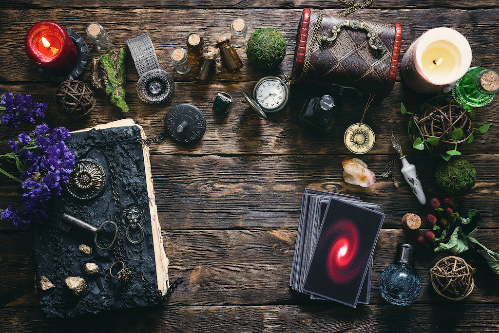 Tarot cards, book of magic and pocket watch on a wooden table background. Future reading.