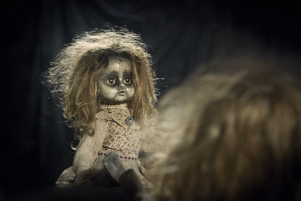 A terrifying doll reflecting creepily in a mirror