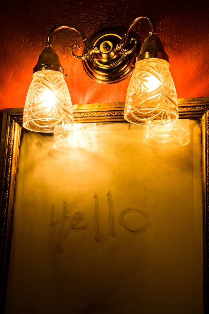 A mirror with ghostly writing on it, light dimly by the lamps overhead