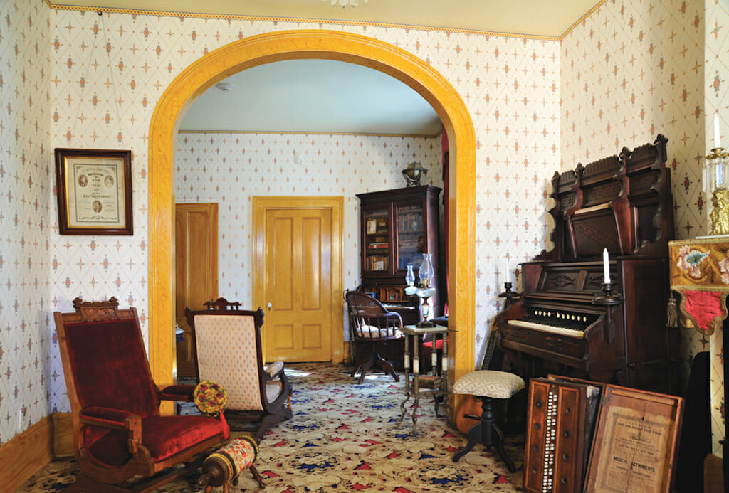 A parlor with cream and yellow wallpaper decorated with warm colored wood furniture