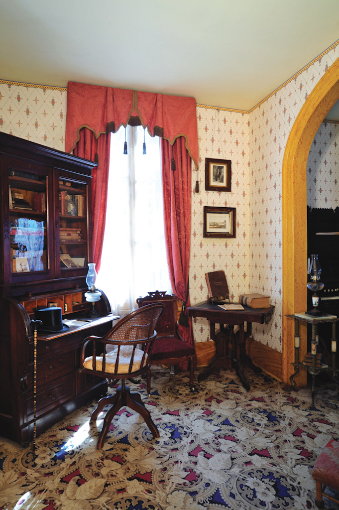A study with cream and yellow wallpaper, windows covered with orange curtains and furnished with warm colored wood furniture