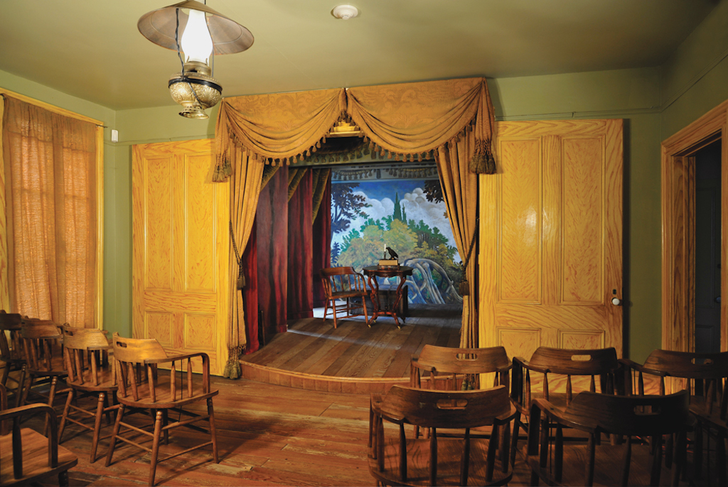 A small theater with dark wood seats, yellow wallpaper and curtains, and bright lighting
