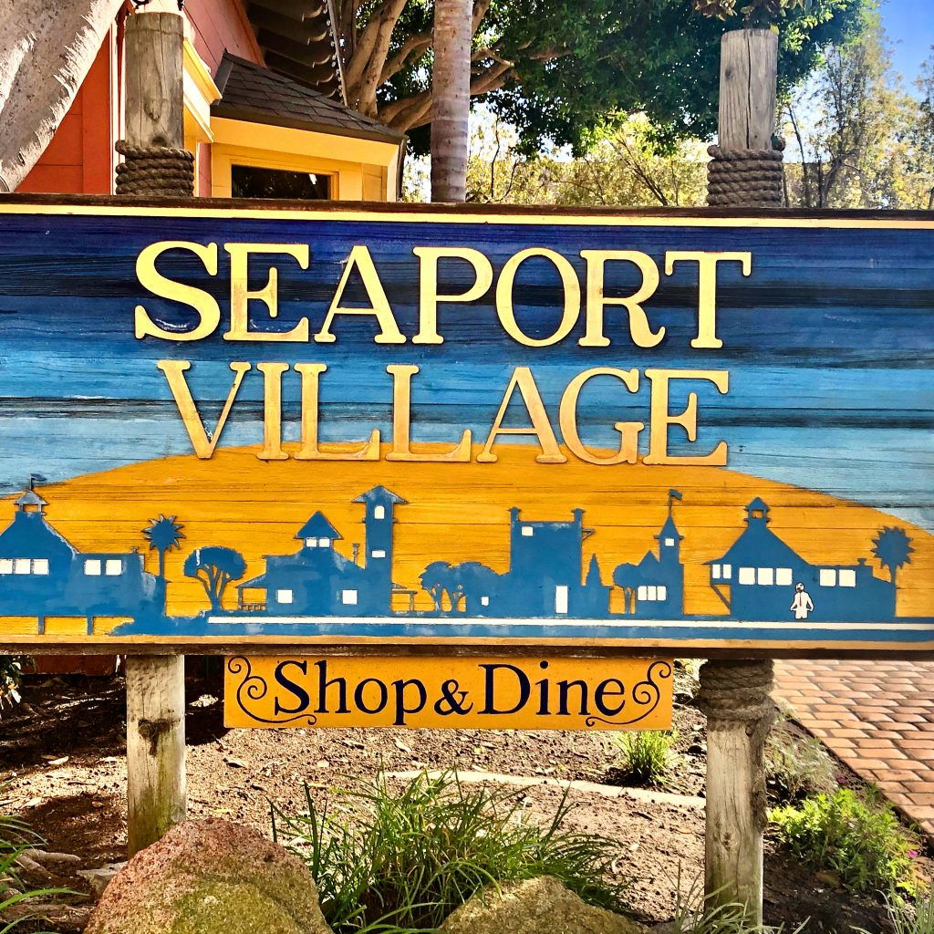 Wood sign in yellow and blue for Seaport Village in San Diego Staycation