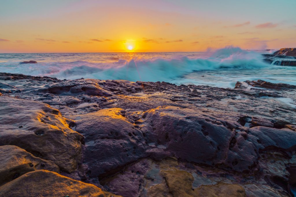 rocks on the beach at sunset with a wave crashing into them
