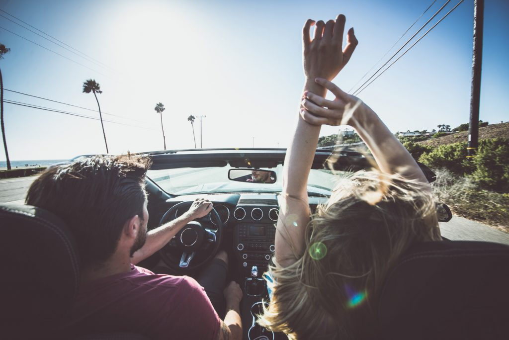 Couple in convertible car driving down the road with hands in the air