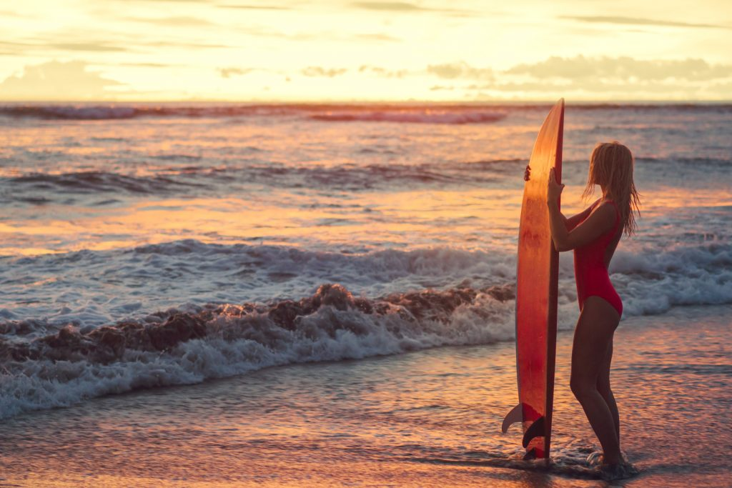 Woman with surfboard standing on the beach at sunset