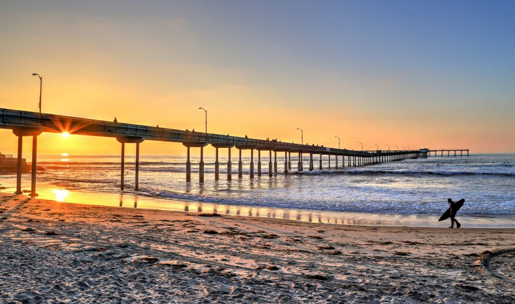 A surfer walks on Ocean Beach near the pier in San Diego, California.