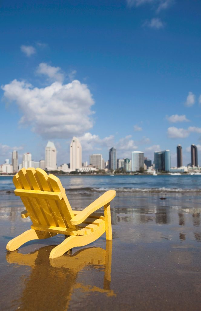 Yellow wood beach chair on the sand at a beach in Coronado with the San Diego Skyline in the Background - San Diego Staycation