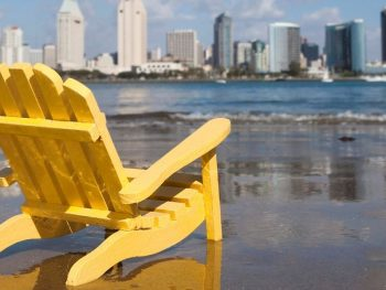 San Diego Staycation - Yellow beach chair on the beach in Coronado with the San Diego Skyline in the background
